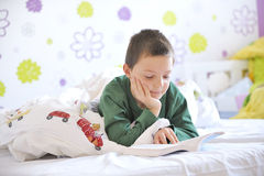 Young boy in his bed reading a book Stock Photos