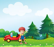 A young boy beside his car at the hill Royalty Free Stock Image