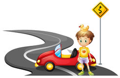 A young boy and his car at the road near the yellow signboard Royalty Free Stock Photo