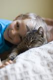 Young boy and his cat. A view of a happy young boy snuggled up with his brown cat Stock Photo