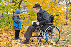 Young boy with his disabled grandfather Royalty Free Stock Photography