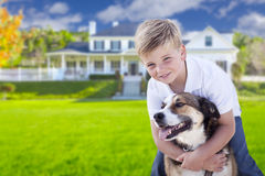Young Boy and His Dog in Front of House. Happy Young Boy and His Dog in Front Yard of Their House Royalty Free Stock Photo