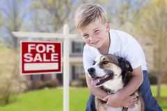 Young Boy and His Dog in Front of For Sale Sign and House. Happy Young Boy and His Dog in Front of For Sale Real Estate Sign and House Royalty Free Stock Photos