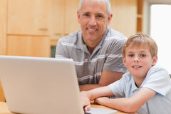Young boy and his father using a laptop. In a kitchen royalty free stock images