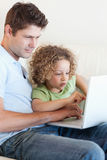 Young boy and his father using a laptop Stock Photos
