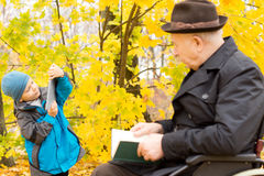 Young boy with his grandfather in an autumn forest Stock Photos