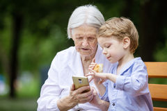 Young boy and his great grandmother using smartphone outdoors Royalty Free Stock Photos