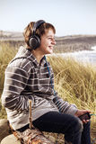 Young boy and his music. Young surfer listening to music down at the beach, enjoying life Stock Photo