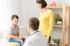 Young boy with his pediatrician and mother. He trusts his pediatrician. Shot of pediatrician discussing health of young boy with his mother by his side Royalty Free Stock Images