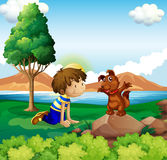 A young boy and his pet near the lake Royalty Free Stock Photo