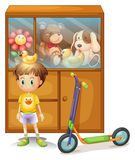 A young boy with his scooter and his toys in a cabinet Royalty Free Stock Photo