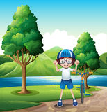 A young boy and his toy bike standing near the trees in the rive. Illustration of a young boy and his toy bike standing near the trees in the riverbank Royalty Free Stock Photos