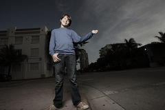 Young boy hitch hiking at night Royalty Free Stock Photos