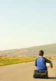 Young boy hitching on road. A boy hitchhikes on the side of the road stock photography
