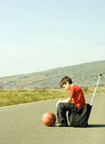 Young boy hitching on road. A boy hitchhikes on the side of the road royalty free stock images