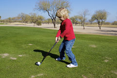 Young Boy Hitting a Drive Royalty Free Stock Photography