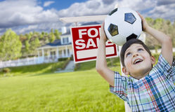 Young Boy Holding Ball In Front of House and Sale Sign. Playful Young Boy Holding Soccer Ball In Front of House and For Sale Real Estate Sign Royalty Free Stock Photography