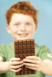 Young Boy Holding Bar Of Chocolate Royalty Free Stock Photo