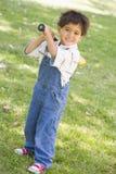 Young boy holding baseball bat outdoors smiling. At camera Stock Photos