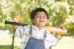 Young boy holding baseball bat outdoors smiling Royalty Free Stock Photos