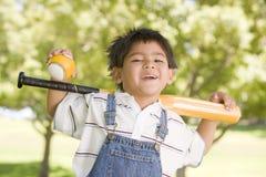 Young boy holding baseball bat outdoors smiling. At camera Royalty Free Stock Photos