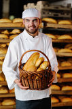 Young boy holding a basket with bakery products. Young handsome man holding a basket of baked goods on background bread store Royalty Free Stock Images
