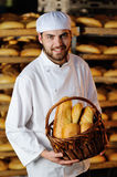 Young boy holding a basket with bakery products. Young handsome man holding a basket of baked goods on background bread store Stock Photos