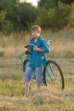 Young boy holding bicycle in farm field Stock Photo