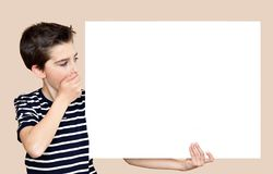 Young boy holding blank white board. Surprised young boy with hand over his mouth holding and looking at the blank white board Stock Image