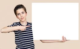 Young boy holding blank white board. Young boy holding and showing with the index finger blank white board Stock Photography