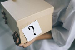 Box with white note question mark - suprise concept. Young boy holding a box with white note question mark. whats in the box Royalty Free Stock Images
