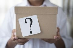 Box with white note question mark - suprise concept. Young boy holding a box with white note question mark. whats in the box Stock Images