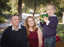 Young Boy Holding Christmas Gift in Park While Parents Look. Handsome Young Boy Holding a Christmas Gift in the Park While His Mom and Dad Look On Royalty Free Stock Photography