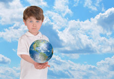 Young Boy Holding Earth and Sky. A young boy is holding the planet Earth in his hands and looks serious. There is a bright blue sky in the background and royalty free stock image