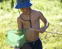 A young boy holding a fishing net Stock Photo