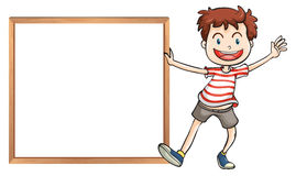 A young boy holding a framed signage Royalty Free Stock Image