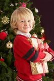 Young Boy Holding Gift In Front Of Christmas Tree Stock Images
