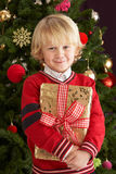Young Boy Holding Gift In Front Of Christmas Tree Royalty Free Stock Photo