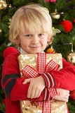 Young Boy Holding Gift In Front Of Christmas Tree Stock Image