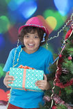 Young boy is holding a gift while standing near the Christmas tree royalty free stock photos