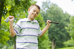 Young boy holding golf clug happy and confident Stock Photos