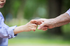 Young boy holding great grandmother`s hand Royalty Free Stock Photography