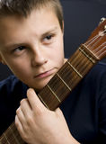 Young boy holding guitar. A portrait of a young boy, holding the neck of a guitar.  Black background Royalty Free Stock Images