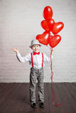Young boy holding a heart-shaped ballon Stock Image