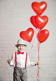 Young boy holding a heart-shaped ballon Royalty Free Stock Photography