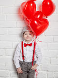 Young boy holding a heart-shaped ballon Stock Images