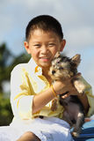 Young boy holding his puppy royalty free stock photos