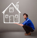 Young boy holding a huge drawn house Royalty Free Stock Images