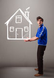Young boy holding a huge drawn house Stock Images