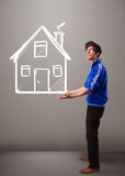 Young boy holding a huge drawn house Royalty Free Stock Image